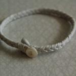 Armband av vitt flätad renskinn med pärlemorknapp