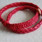Armband eller halsband i rött flätat renskinn med kanpp av pärlemor