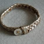 Armband av guldfärgad flätad lamnappa med pärlemorknapp